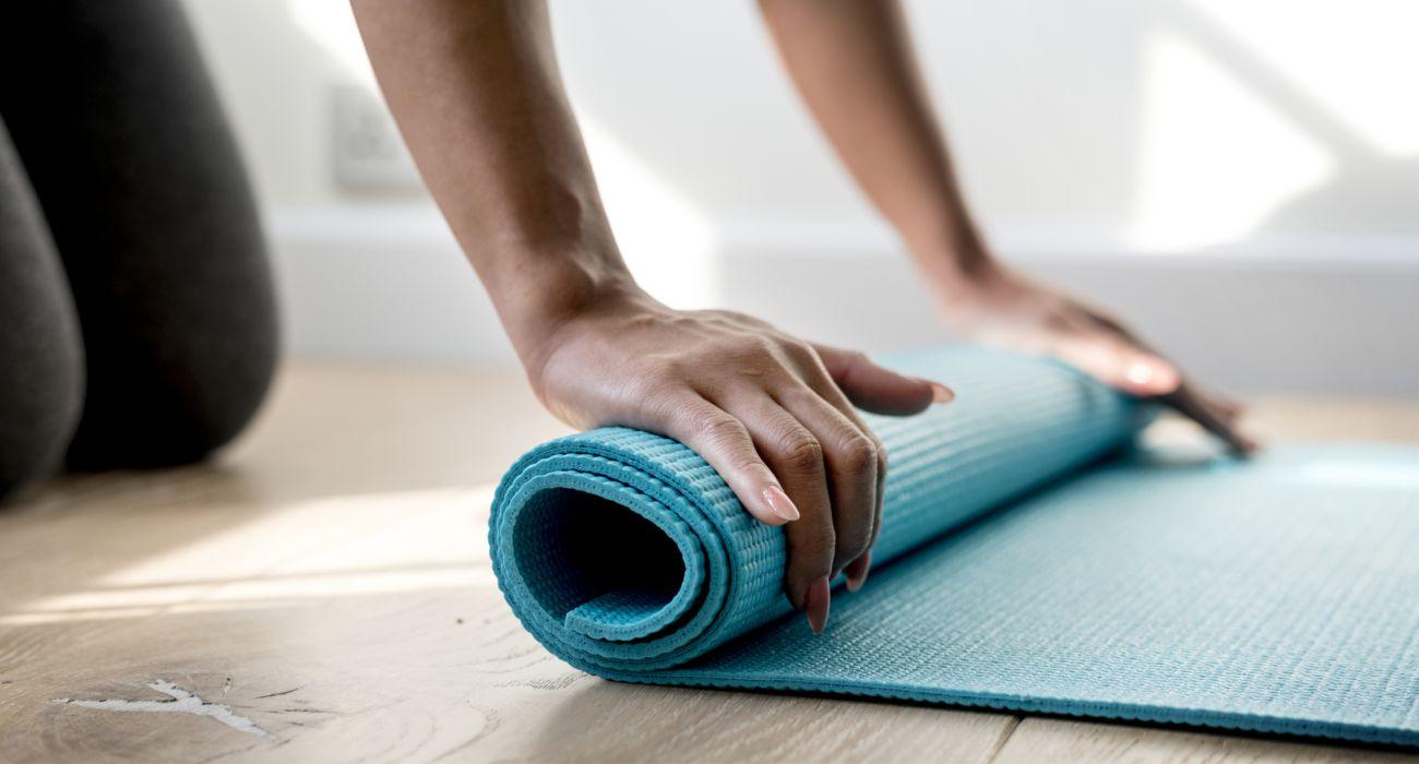 Frau mit Matte - bereitet sich für Yoga vor